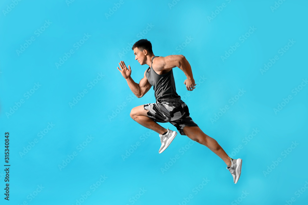 Fototapeta Athletic young man running on light blue background, side view