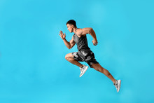 Athletic Young Man Running On Light Blue Background, Side View