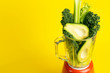 Leinwanddruck Bild - Smoothie recipe. Green smoothie of vegetables (avocado, celery, cale salad, spinach) in a blender on a yellow background. Vegan and healthy food detox concept
