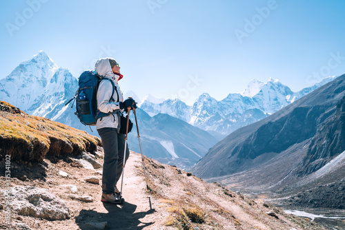 Fototapeta Young hiker backpacker female taking a walking with trekking poles during high altitude Everest Base Camp route near Dingboche,Nepal. Ama Dablam 6812m on background. Active vacations concept obraz