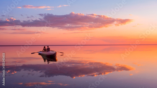 Fototapeta krajobraz   a-couple-in-love-look-at-beautiful-sunset-in-a-rowing-boat-on-the-lake-pink-sky-and-vanilla-clouds-romantic-scene-lovers-ride-a-boat-in-nature-during-sunset-amazing-landscape-with-people