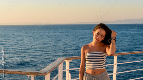 Stampa su Tela Teen girl in shorts on deck of ferry boat holding hair