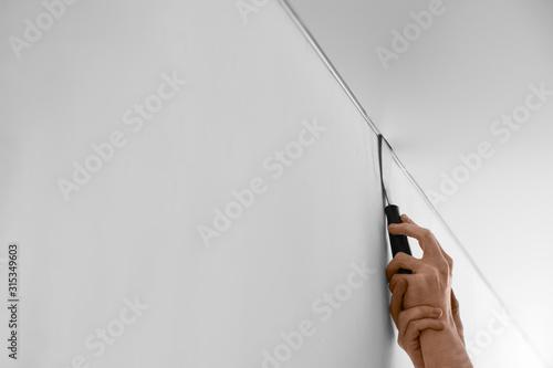 Cuadros en Lienzo  Repairman installing white stretch ceiling in room, closeup