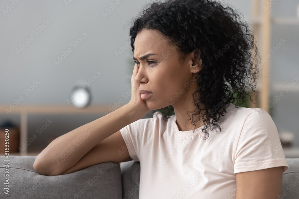 Fototapeta Side closeup view african sad pensive woman sitting on couch