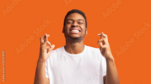 Hopeful african american guy crossing his fingers Tableau sur Toile