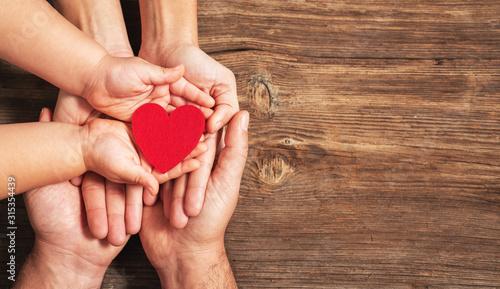 Fotografie, Obraz family hands holding red heart on wooden background