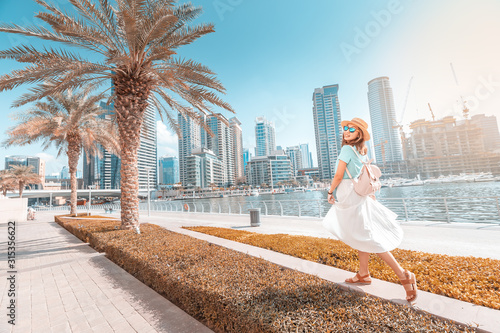 Fotografie, Obraz Happy asian girl walking on a promenade in Dubai Marina district