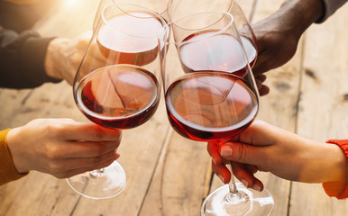 Hands toasting red wine glass and friends having fun cheering at winetasting experience - Young people enjoying time together at wine degustation - Youth and friendship concept
