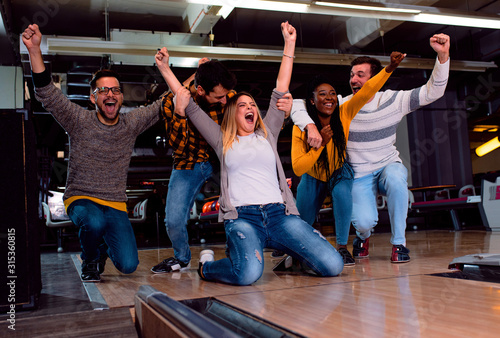 Group of friends enjoying time together laughing and cheering while bowling at club Tablou Canvas