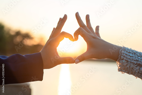 Women and men hands In the form of hearts against the sky through the sun's rays Wallpaper Mural