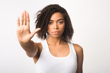 Black girl showing stop sign on white background