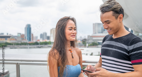 Photo Young asian couple making acquaintance relaxing along the city and using their s