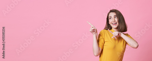 Fototapeta Beautiful healthy young woman smiling with his finger pointing and looking at on light pink banner background with copy space. obraz