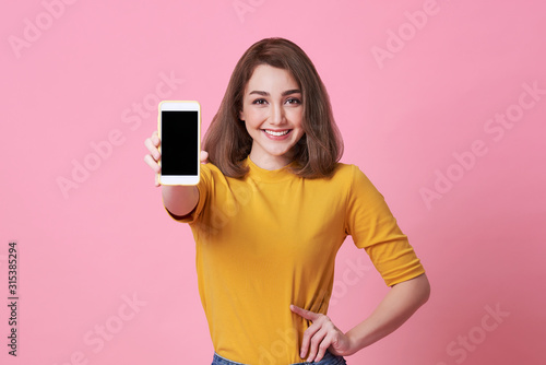 Obraz Portrait of happy young woman showing at blank screen mobile phone isolated over pink background. - fototapety do salonu