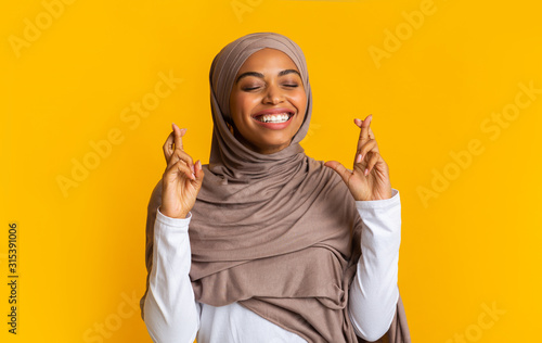Photographie Positive afro muslim woman in hijab making wish with crossed fingers