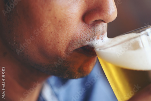 Fototapeta The young man's lips tasting the beer's flavors and feeling the softness of the beer bubbles. obraz