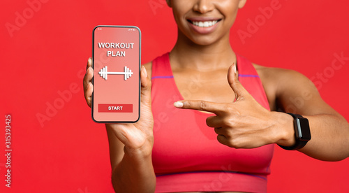 Obraz Fitness lady pointing at workout application on phone screen - fototapety do salonu