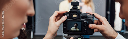 Obraz panoramic shot of digital camera with photo of handsome model near art director and photographer - fototapety do salonu