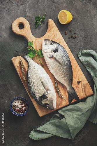 Fotografie, Obraz Fresh raw dorado fish, lemon and spices on a wooden cutting board, dark rustic background