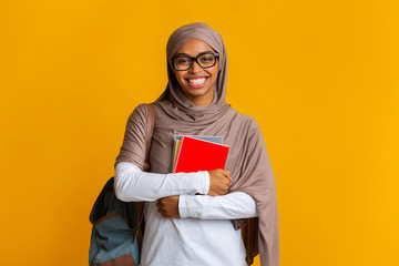 Happy black muslim student girl in hijab with backpack and notepads