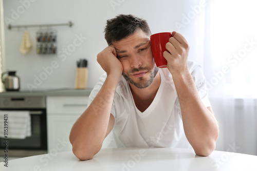 Fotografie, Obraz  Sleepy man with cup of drink at home in morning