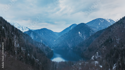 Winter lake Ritsa in Abkhazia with mountains in the snow in the background, late evening Wallpaper Mural