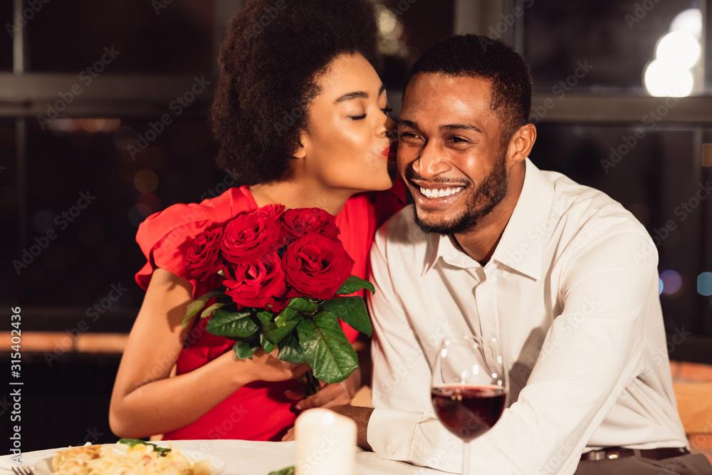 Fototapeta Girlfriend Kissing Boyfriend After Receiving Roses During Date In Restaurant