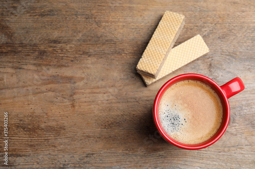 Fototapeta Breakfast with delicious wafers and coffee on wooden table, flat lay. Space for text obraz