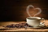 Filiżanka kawy z kierowym kształta dymem i kawowymi fasolami na burlap worku na starym drewnianym tle