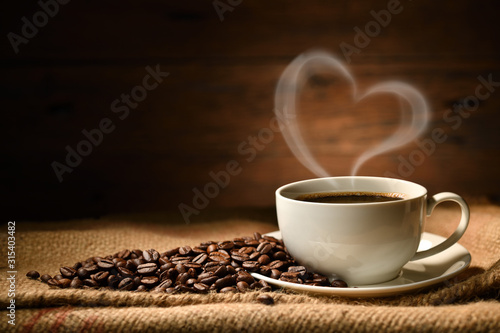 Canvas Print Cup of coffee with heart shape smoke and coffee beans on burlap sack on old wood