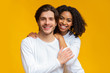 canvas print picture - Romantic interracial couple embracing and posing over yellow background
