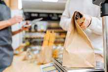 Woman Chooses And Buys Products In Zero Waste Shop. Weighing Dry Goods In Plastic Free Grocery Store. Girl With Cotton Reusable Bag Weigh Paper Bag On Scales. Eco Shopping At Local Business