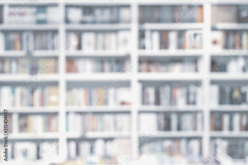 Fototapeta Abstract blurred bookshelves with books, manuals and textbooks on bookshelves in library or in book store, soft focus