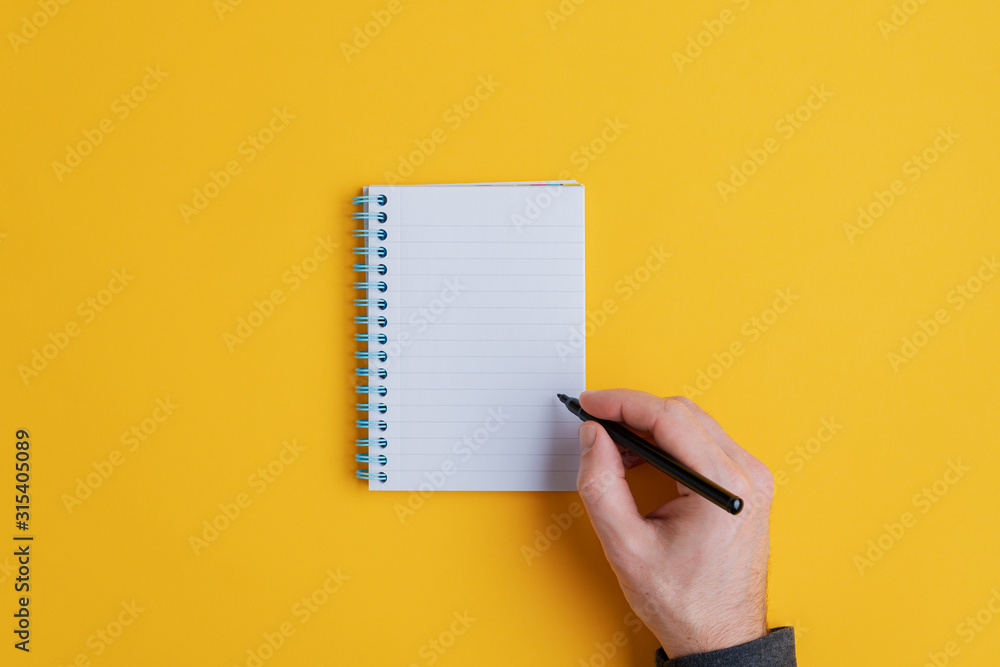 Fototapeta Male hand about to write in notebook