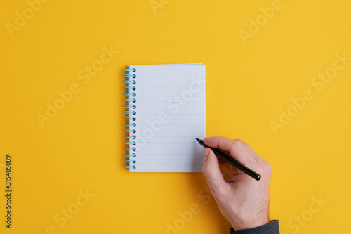 Male hand about to write in notebook Canvas Print