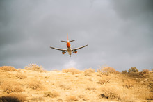 From Below Of White And Orange Aircraft Flying With Cloudy Grey Sky On Background