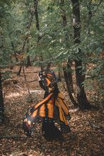 Side View Of Young Woman In Butterfly Wings Cape Dancing Near Trees In Green Forest