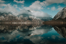Serene Stunning Landscape Of Motionless Lake Reflecting Bright Cloudy Sky Surrounded By Snowy Mountain In Hallstatt