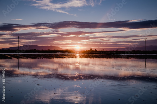 Spectacular landscape with sun setting behind mountains and clouds and reflecting in calm water of river delta with fisherman sticks