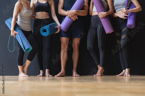 Fototapeta Group of young sporty man and women with yoga mats standing at black wall smilin