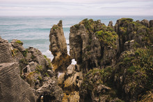 From Above Of Rocky Overgrown Of Plants Seashore With Waves And Cloudy Sky In Pancake Rocks In New Zealand