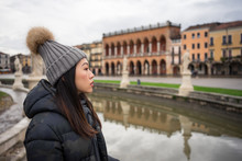 Side View Of Young Asian Resting Lady In Warm Clothing And Hat Walking At Beautiful Prato Della Valle Park At Padova At Italy