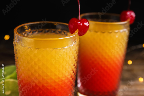 Fotomural  Fresh alcoholic Tequila Sunrise cocktails on wooden table, closeup