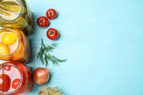 Glass jars with different pickled vegetables on light blue wooden table, flat lay Wallpaper Mural