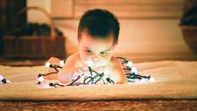 Baby Playing With Light Garlan...