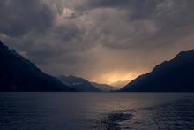 Calm Landscape Of Dark Rippled Water Under Gray Cloudy Sky In Mountains In Switzerland