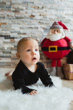 Funny Baby In Pajama Looking Away While Lying On Soft Carpet Near Toy Santa Claus During Christmas Celebration At Home