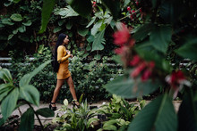 Side View Of Trendy Asian Woman With Long Dark Hair In Yellow Shirt And Short Skirt Walking In Beautiful Garden And Looking Away