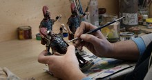 Side View Of Crop Person Painting Clay Figurines Of Soldiers With Brush At Table In Pottery