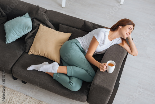 Fototapeta overhead view of attractive woman chilling of sofa with cup of tea obraz